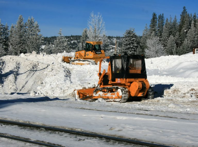 bulldozers push snow away from the railroad tracks