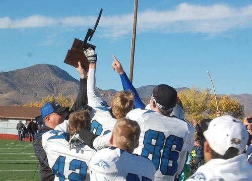 Pahranagat Valley coach Ken Higbee holds the state championship trophy high for the team in 2015, as they won a record eighth straight NIAA title