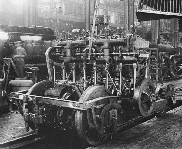 The McKeen motor car's 6-cylinder overhead-valve gasoline engine was a source constant irritation to the V&T's motormen and mechanics. It was hard to start and so rough-running that it required a massive flywheel at the end of the crankshaft to keep it from stalling. In order to reverse the direction the car moved in the engine first had to be shut down, after which the tall lever protruding from the upper center of the engine -- connected to two sliding camshafts on either side of the engine, each with two sets of cams -- had to be moved. This changed the valve timing , so that when restarted the engine would then rotate in the opposite direction. --- Editor