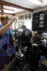 Museum Director Elsbeth Kuta with antique movie projector from the Elward Theatre