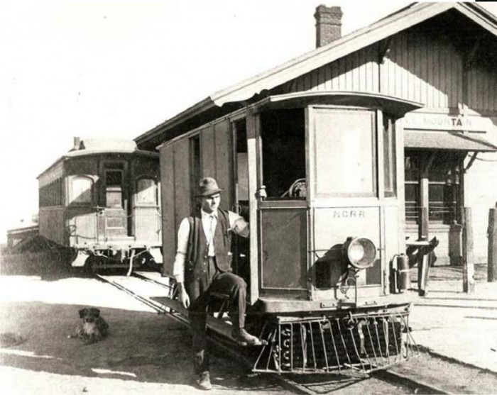 A motorman and his dog pose with Nevada Central Railroad No. 102 at the Battle Mountain Depot