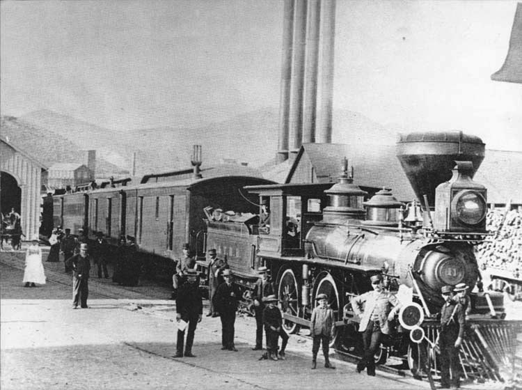 "The ""Reno"" at the V & T passenger depot on E Street, Virginia City. The large building with four smokestacks in the background is the hoisting works of the Consolidated Virginia Mine. (Courtesy CalNeva Photo Collection)"
