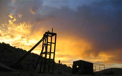 Saloon and mine derrick at sunset